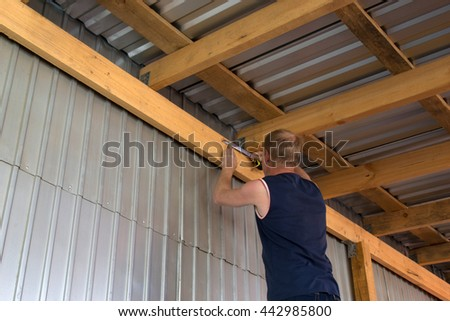 Work takes measurements on the ceiling beam - stock photo