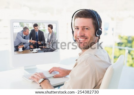 Work team having a meeting together against businessman in headset smiling at camera - stock photo