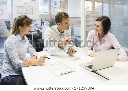 Work team in meeting room working on laptop - stock photo