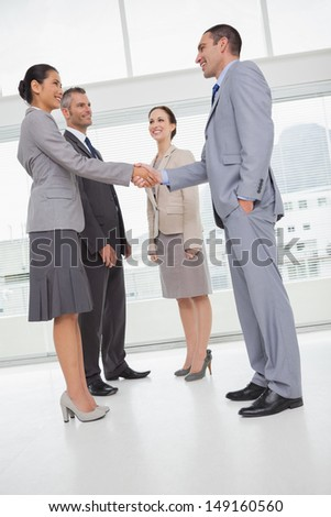 Work team shaking hand with their new partner in bright office - stock photo