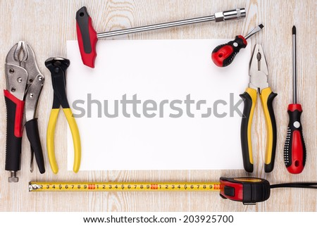 Work tools and a sheet of paper on wooden texture. - stock photo