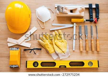Work tools for carpenter. Top view of diverse working tools for wood industry laying on the wood grain - stock photo