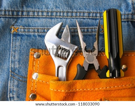 Work tools in orange tool bag with jeans. - stock photo
