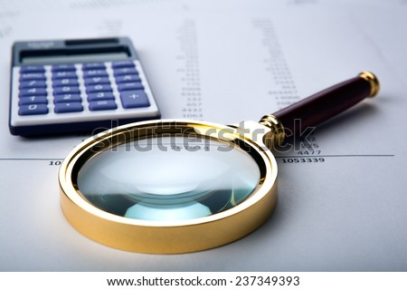 work with a magnifying glass, a calculator and papers