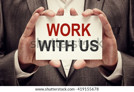 Work with us. Businessman holding a card with a message text written on it