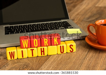 Work With Us written on a wooden cube in a office desk - stock photo