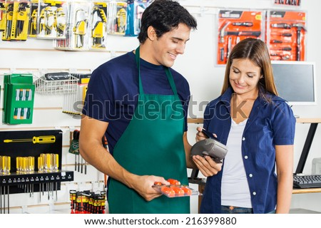 Worker accepting payment through smartphone from woman in hardware store - stock photo