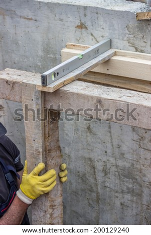 worker adjusts level of wooden framework installation at construction site - stock photo