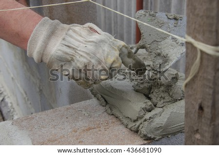 worker aligns with a spatula, lay brick cinderblocks - stock photo