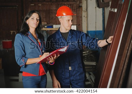 worker and a female chief accounting the metal profiles in stock