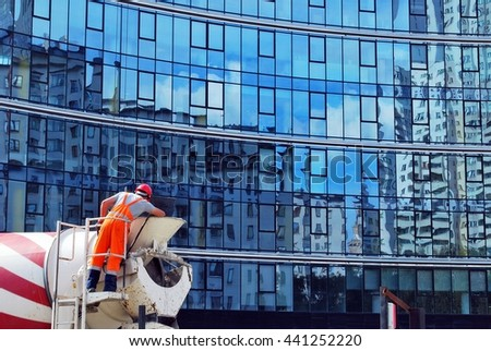 Worker and concrete mixer truck pouring cement at construction site - stock photo