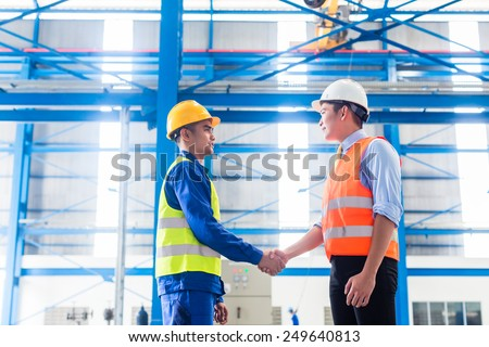 Worker and customer having agreement in factory shaking hands