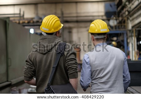 Worker and engineer working inside a factory - stock photo