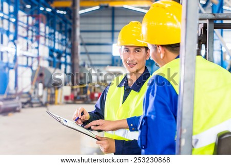 Worker and forklift driver in industrial factory looking at camera - stock photo