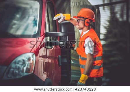 Worker and His Truck. Hard Working Men Wearing Construction Safety Accessories.