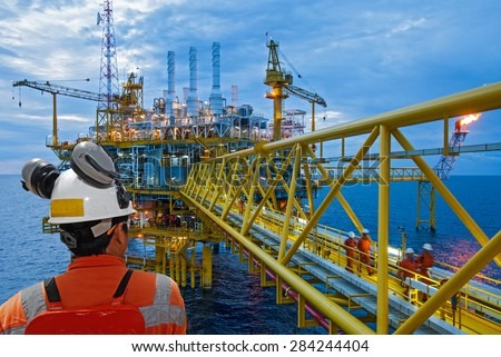 worker and oil rig background. business concept. - stock photo