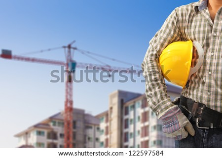 Worker and the blurred construction background in blue sky - stock photo