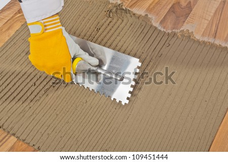 worker applied tile adhesive on old wooden floor - stock photo