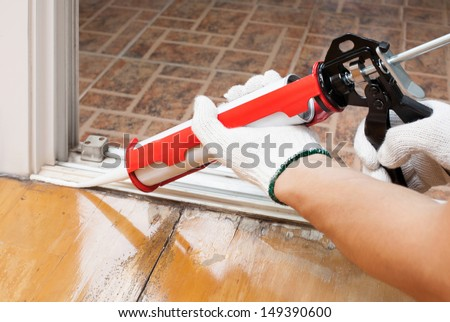 Worker applies silicone caulk on the wooden floor for sealant waterproof  - stock photo