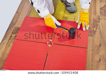 Worker Applies with Rubber Hummer Tile on a wooden Floor reinforced mesh - stock photo