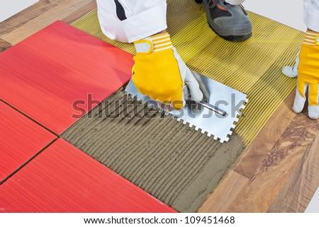 worker apply ceramic tiles on wooden floor mesh trowel - stock photo