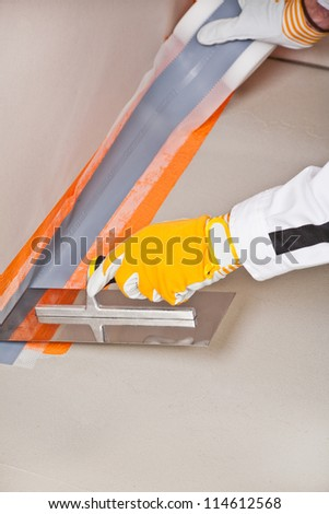 worker apply hydro insulation tape around the wall and floor - stock photo