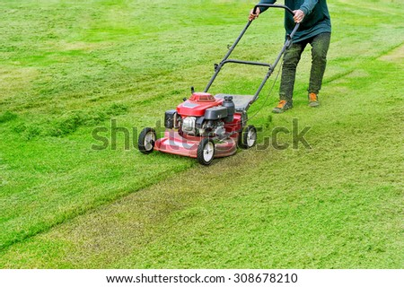 Worker are working with lawn mower. - stock photo
