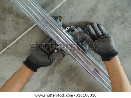 Worker assembles profile metal frame for plasterboard ceilings
