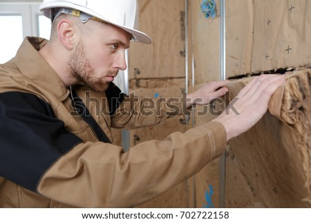 worker at a indoors wall insulation works