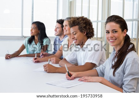Worker at board meeting smiles to camera in the office
