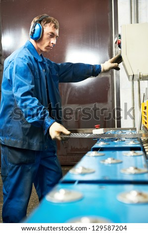 worker at manufacture workshop operating guillotine shears machine - stock photo