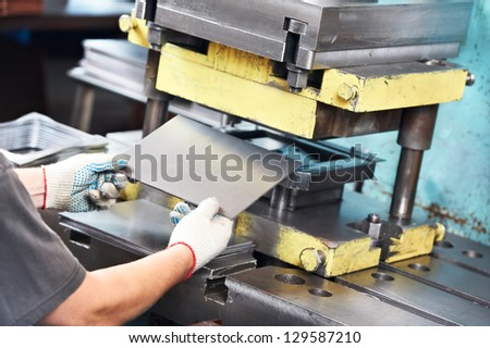 worker at manufacture workshop operating metal press machine - stock photo