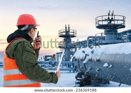 Worker at the oil field , natural gas storage in the background.Refinery , oil and natural gas  - stock photo