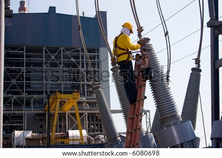 Worker at the switch yard for maintenance work with power plant at the background - stock photo