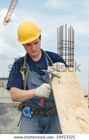 Worker builder at construction site working with plywood board and hammer