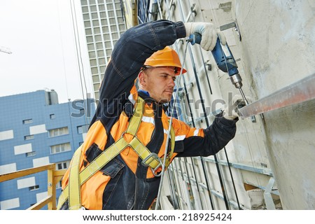 worker builder making construction for ventilation facade on a building with screwdriver drill - stock photo