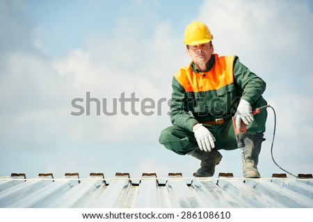 worker builder with hand drill at metal profile roof installation - stock photo