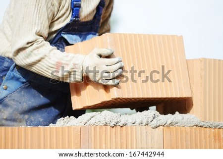 Worker building on wet layer concrete, brick wall - stock photo