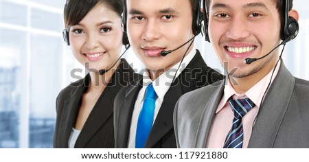 worker call center smiling with colleague in background - stock photo