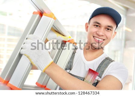 Worker carrying a ladder working in building construction - stock photo