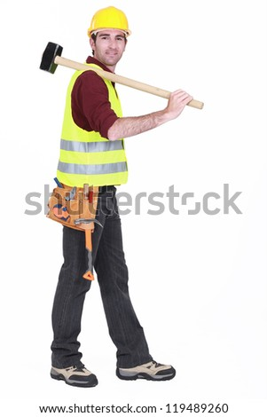 Worker carrying sledge-hammer over shoulder - stock photo