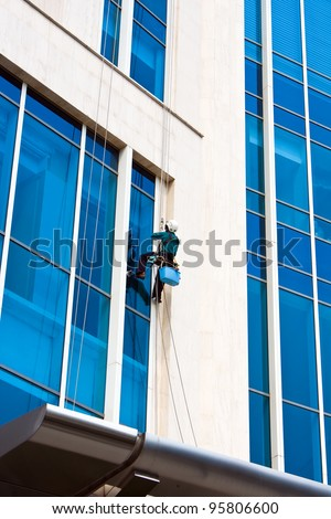 Worker clean mirror on high building