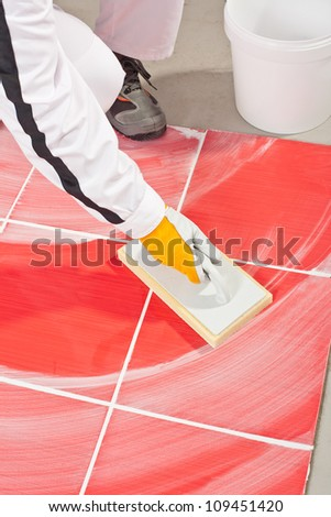 worker clean with sponge trowel tile joints grout - stock photo