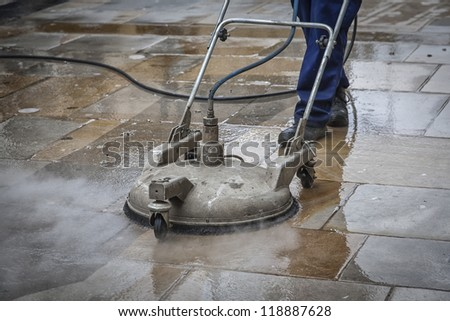 Worker cleaning a pavement in Oxford, England by steam. - stock photo