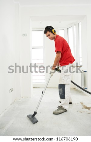 Worker cleaning floor with vacuum cleaner from industrial concrete dust and cement dirt during home renovation work - stock photo