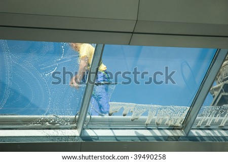 worker cleaning glass roof of modern building - stock photo