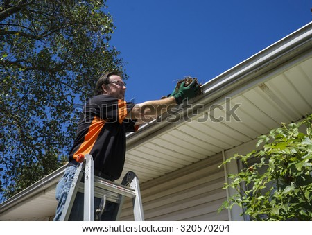 Worker cleaning gutters on a customers home. - stock photo
