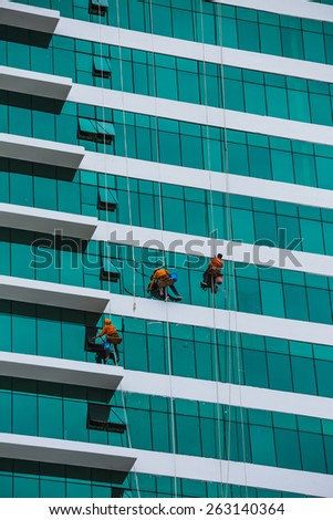 worker cleaning high tower in big city, Vietnam. - stock photo