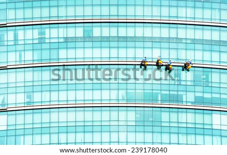 worker cleaning high tower in Ho Chi Minh city, Vietnam. - stock photo