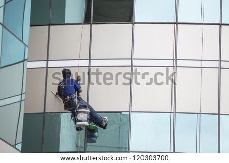 worker cleaning high tower with green glass - stock photo